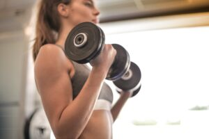 Brunette Caucasian doing bicep exercise by lifting barbells